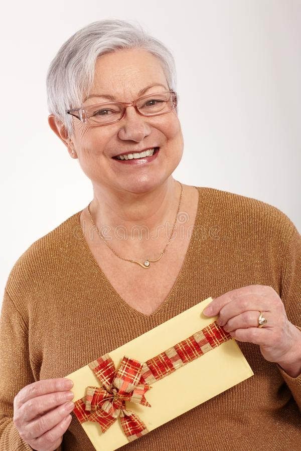 Happy old lady with present. Happy old lady holding fancy present in hand, smiling, looking at camera stock images