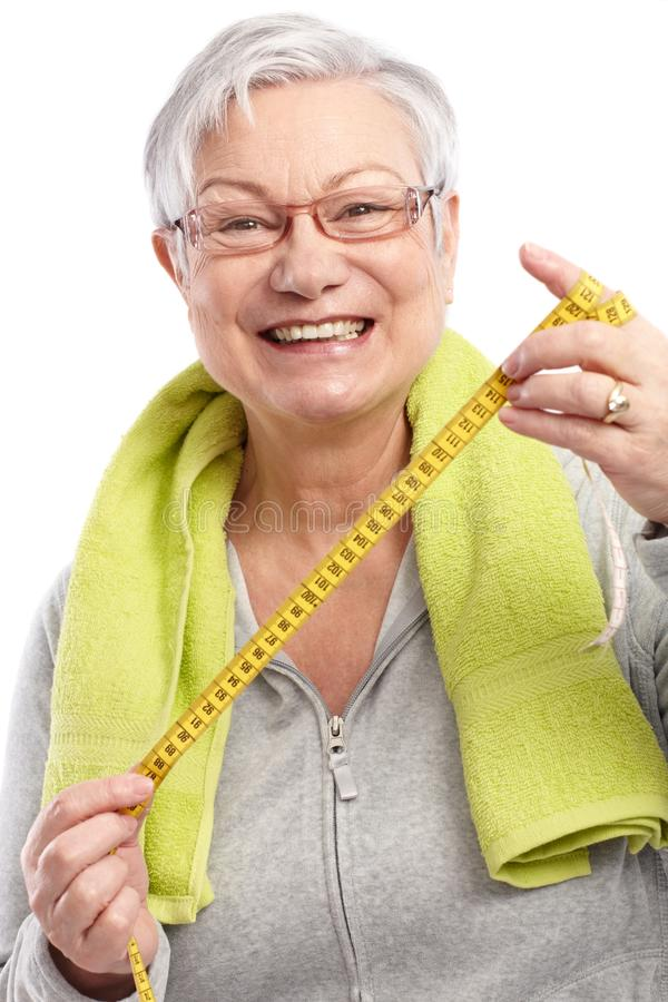 Happy old lady with tape measure. Happy old lady holding tape measure, towel around neck, smiling stock images