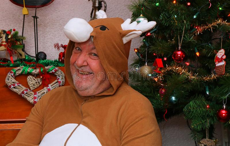 Happy old man at Christmas time wearing onesie. A very happy senior man dressed in a reindeer suit and sitting by a Christmas tree. Having fun and smiling royalty free stock photography