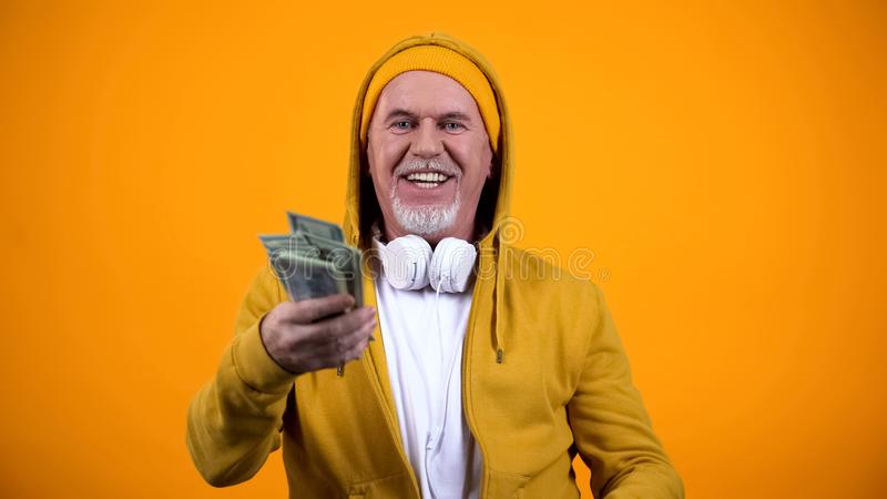 Happy old man in earphones and stylish clothes holding dollars and having fun stock photos