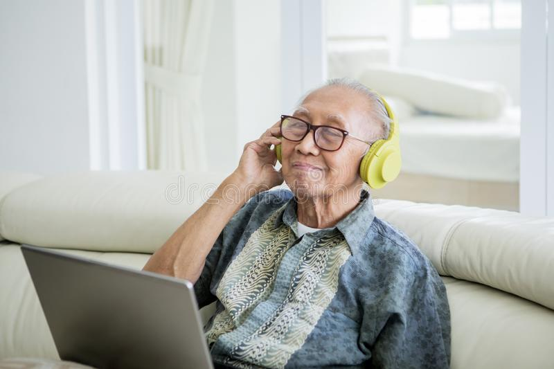 Happy old man enjoying music with headphones. And laptop while sitting on the sofa at home stock photos