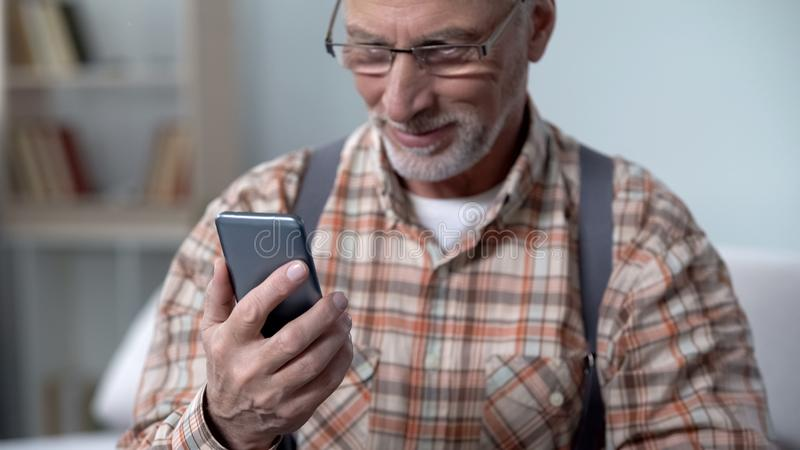 Happy old man holding phone, learning modern technologies, easy app for elderly stock photo
