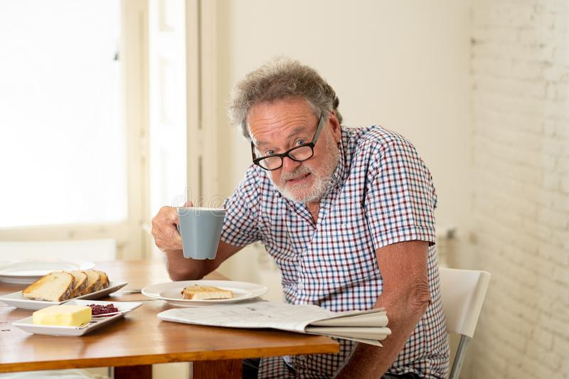 Happy old man reading the newspaper while having breakfast royalty free stock photography