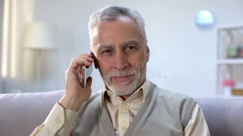 Happy old man receiving good news on cellphone, cheap mobile provider, roaming. Stock photo royalty free stock images