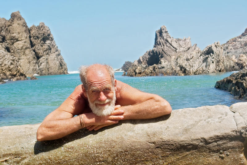 Happy old man rests on beach royalty free stock images
