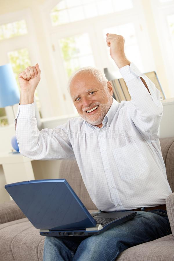 Free Happy Old Man Sitting On Sofa With Laptop Stock Photography - 27720792
