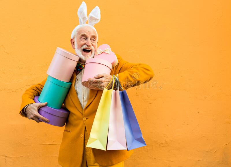 Happy old man standing with present boxes stock photo