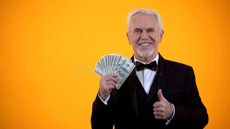Happy old man in suit holding dollars and showing thumbs-up, business income royalty free stock photos