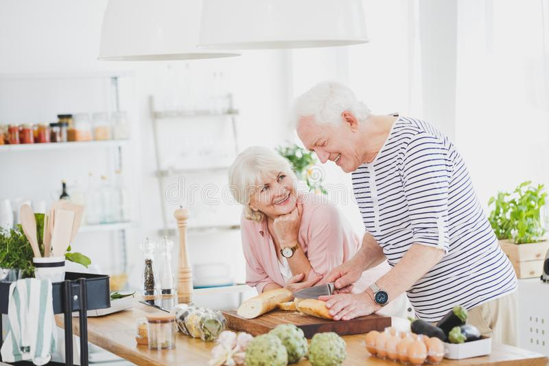 Happy old man cuts the baguette. Happy old men cuts the baguette on a wooden kitchen board when his wife watches him stock image