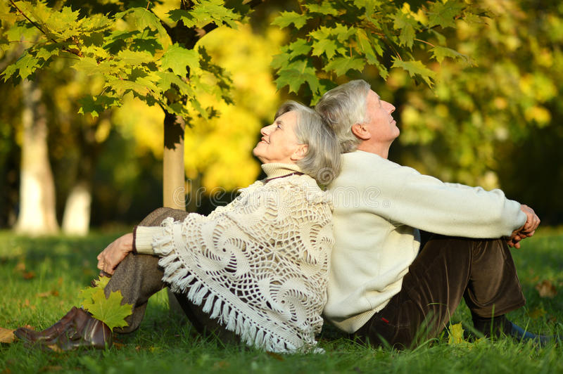 Happy old people. Beautiful happy old people sitting in the autumn park stock image