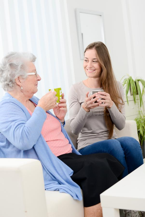 Happy old senior woman spending time and drinking tea with cheerful young girl at home. Happy old senior women spending time and drinking tea with a cheerful royalty free stock image