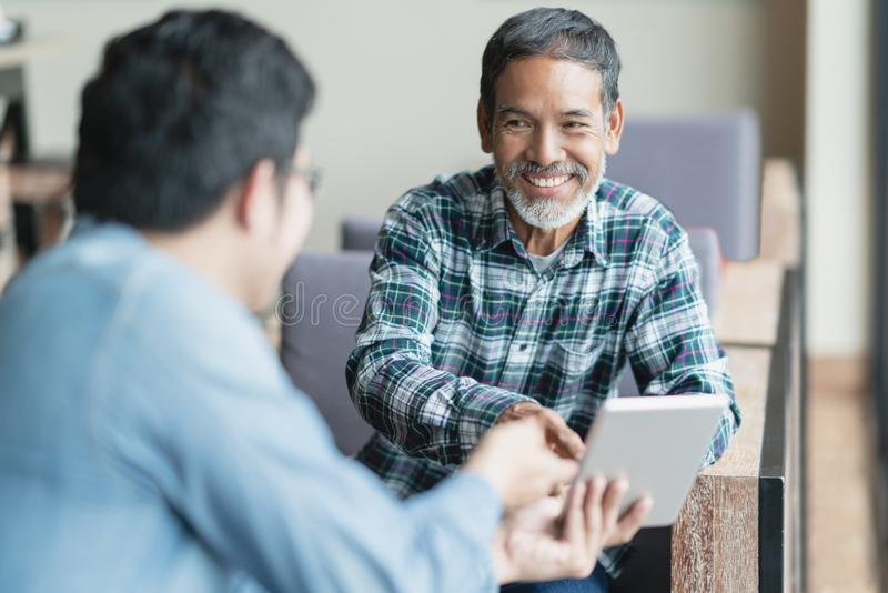 Happy old short beard asian man sitting, smiling and listen to partner that showing presentation on smart digital tablet. royalty free stock image
