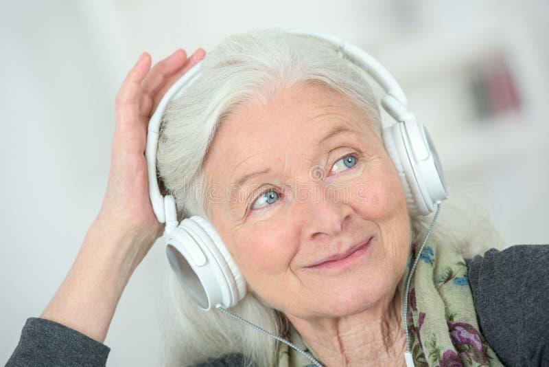 Happy old woman with headphones stock photo