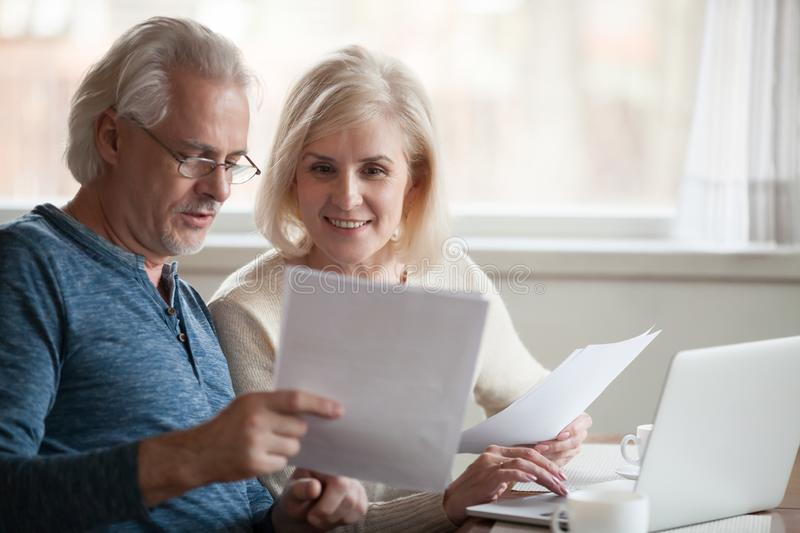 Happy older aged couple holding reading good news in document. Happy old middle aged couple holding reading good news in document, smiling senior mature family royalty free stock photography