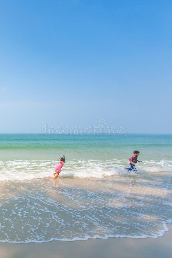 Happy older brother and little sister playing and surfing on white sand beach, light blue sky backgrounds. Summer season. Sunny royalty free stock photography