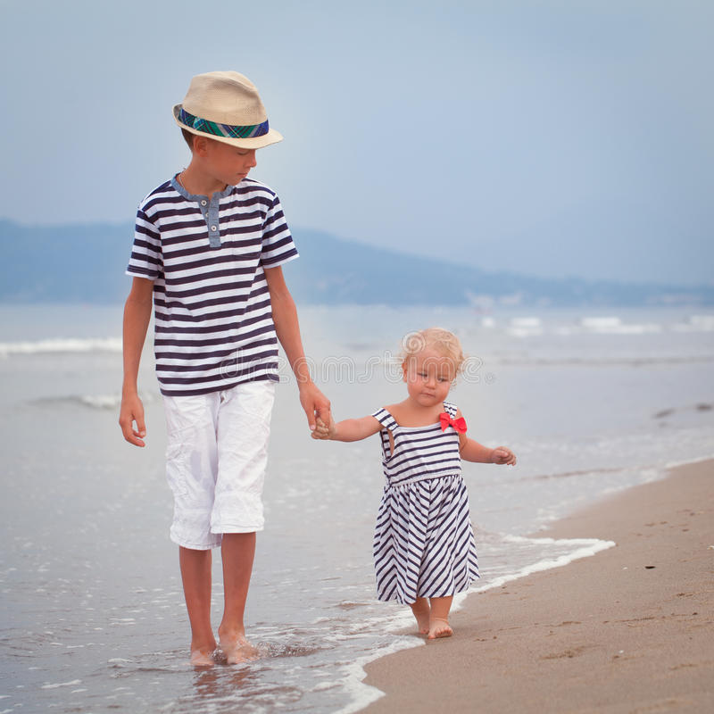 Happy older brother and younger cute sister walking on sea coast royalty free stock image
