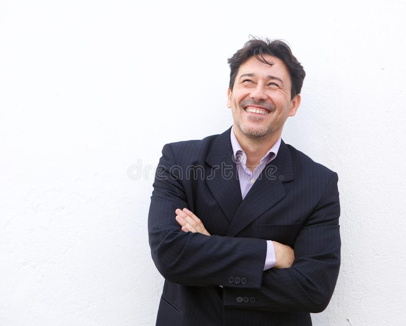 Happy older businessman smiling against white background and looking away at copy space stock image