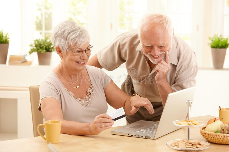 Happy older couple doing online shopping. Laughing wife pointing at screen of laptop computer stock photo