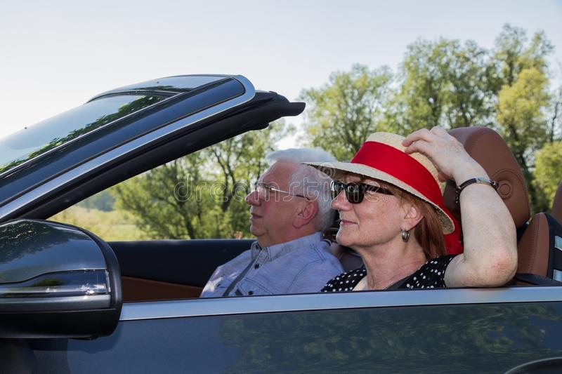 Happy older couple drives with a luxury convertible car. On a sunny day stock photos