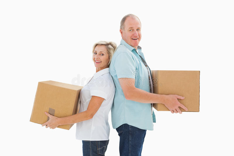 Happy older couple holding moving boxes stock image