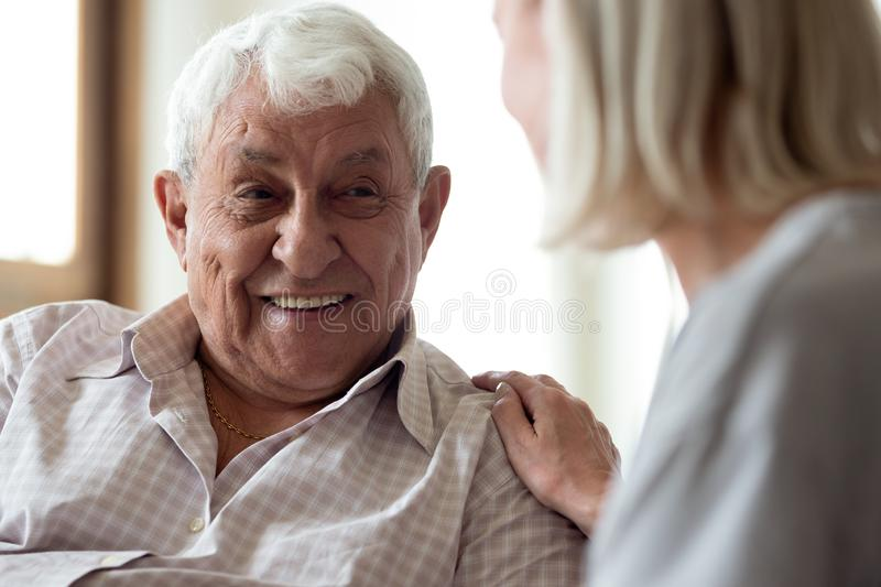 Smiling elder male patient communicating with nurse. royalty free stock photos