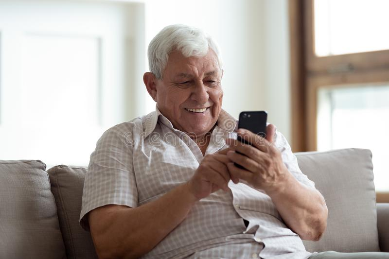 Happy older man sitting on sofa at home, using smartphone. stock photography