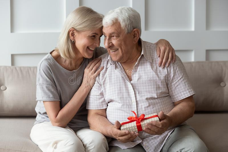 Happy older 70s man feeling thankful to wife for present. Happy older 70s men feeling thankful to smiling attractive mature wife for prepared wrapped gift stock photos