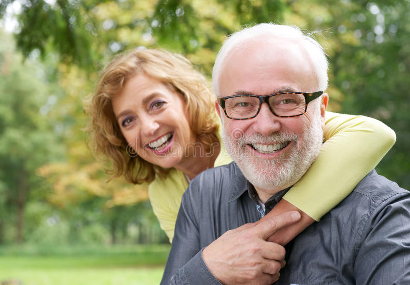 Happy older woman embracing smiling older man stock images