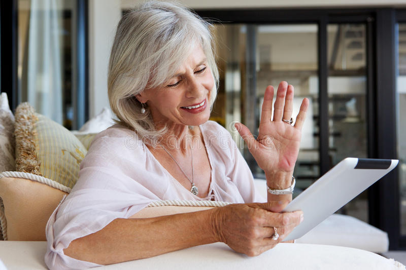 Happy older woman at home with touch screen tablet royalty free stock photography