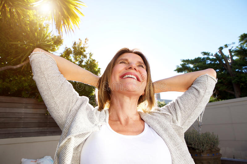 Happy older woman smiling with hands behind head royalty free stock photos