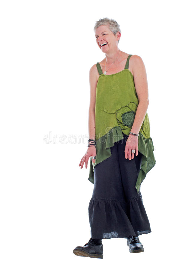 Happy older woman stands in flowing long dress. Cheerful friendly older woman stands in loose flowing long green linen two piece dress with ruffle. She has short royalty free stock photography