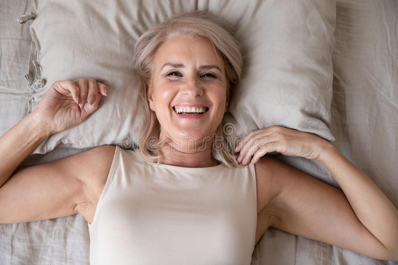 Happy older woman wake up in bed, top view stock photos