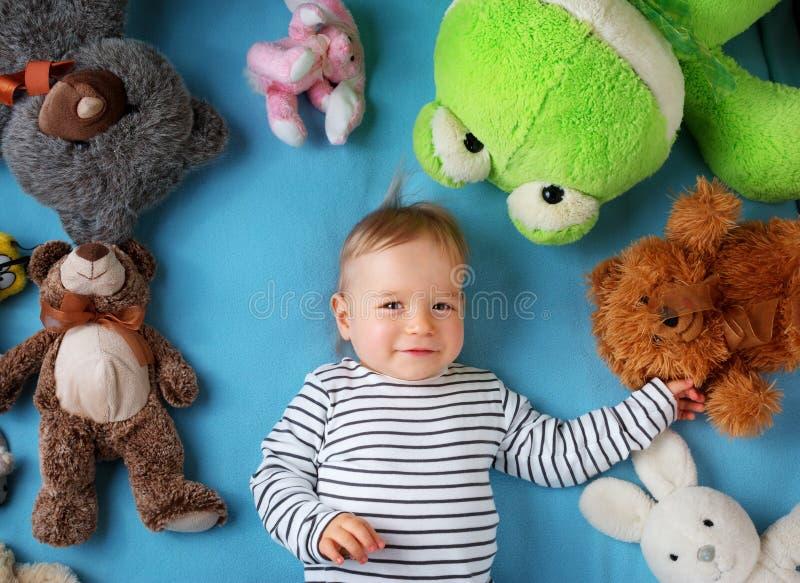 Happy one year old boy lying with many plush toys stock image