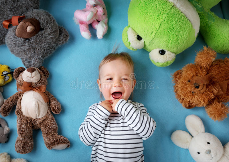 Happy one year old boy lying with many plush toys royalty free stock image