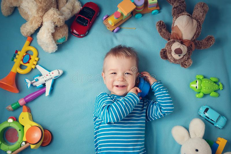 Happy one year old boy lying with many plush toys royalty free stock images