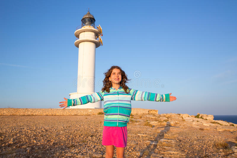 Happy open arms kid girl in Mediterranean lighthouse. At formentera stock images