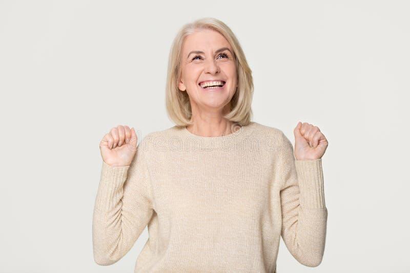 Happy overjoyed middle aged woman celebrating win isolated on background. Happy overjoyed middle aged older woman celebrating fortune bid win victory success stock images