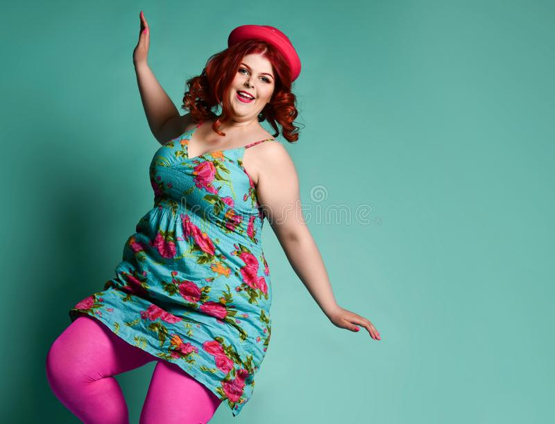 Happy overweight fat chubby woman in funny hat and colorful clothes dances on popular mint royalty free stock image