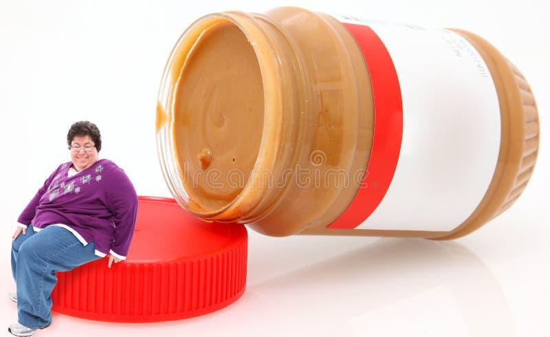 Happy OverwieghtWoman Sitting on Peanut Butter Jar stock photo