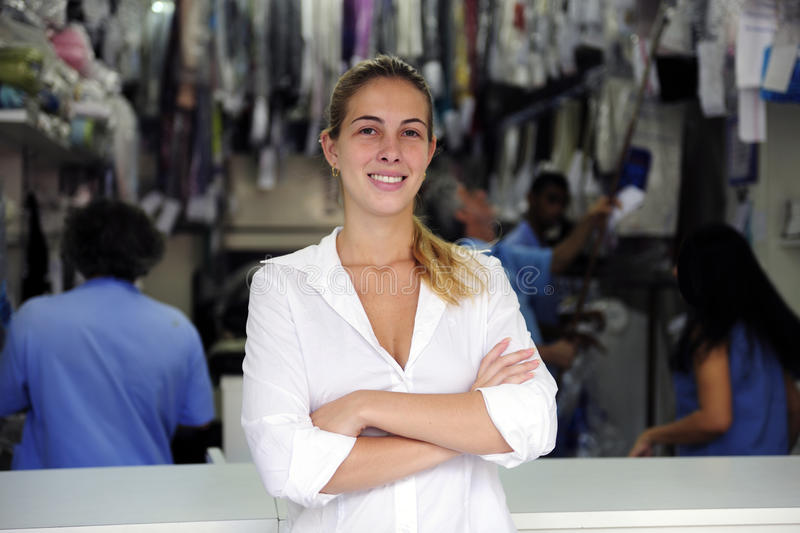 Happy owner of a dry cleaning business. Small business: happy owner of a dry cleaning service royalty free stock photo