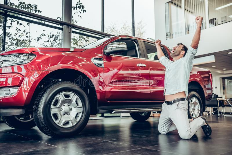 Happy owner of new automobile kneeling, posing and holding hands up. Bearded man standing on knees before red big car. Customer buying vehicle in modern car royalty free stock images