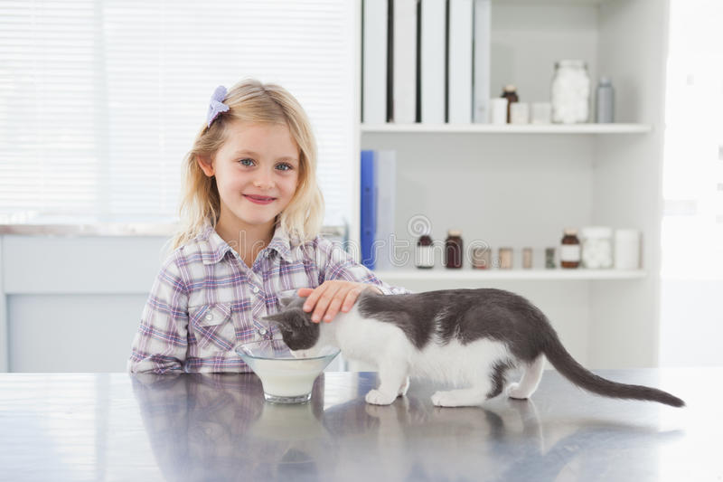 Happy owner petting her cat drinking milk. In medical office royalty free stock photos