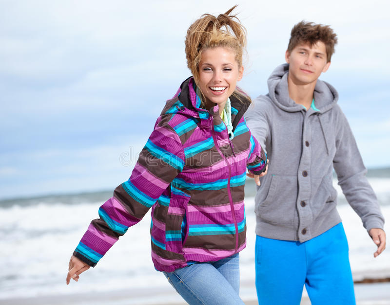 Happy pair on beach. Happy pair of male and female embracing and having fun wearing warm clothes outside on coast behind blue sky royalty free stock photo