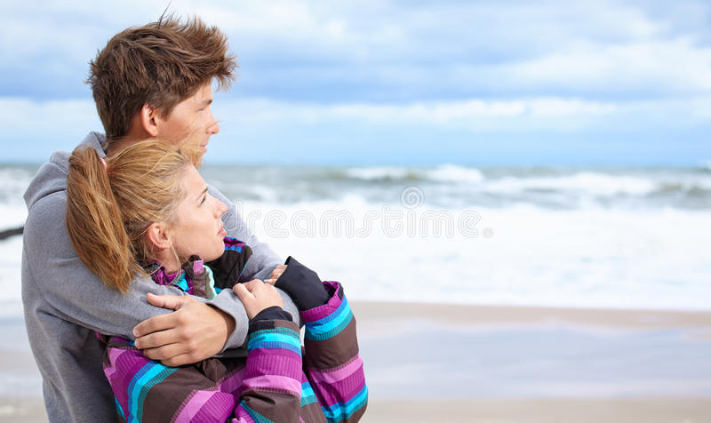 Happy pair on beach. Happy pair of male and female embracing and having fun wearing warm clothes outside on coast behind blue sky royalty free stock images