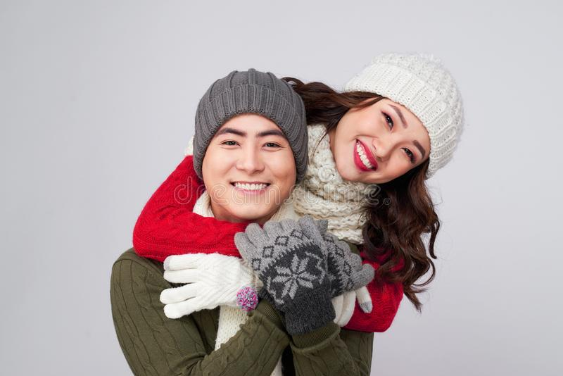 Happy pair of male and female having fun wearing warm clothes royalty free stock image