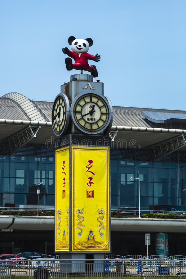 Happy Panda Airport Clock. Under a clear blue sky, a statue of a smiling, happy panda running in a red suit sits atop a clock tower with yellow panels bearing stock photos