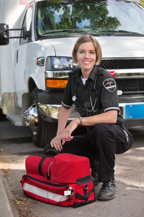 Happy Paramedic Portrait. Portrait of a happy paramedic kneeling by a portable oxygen unit and ambulance royalty free stock photography