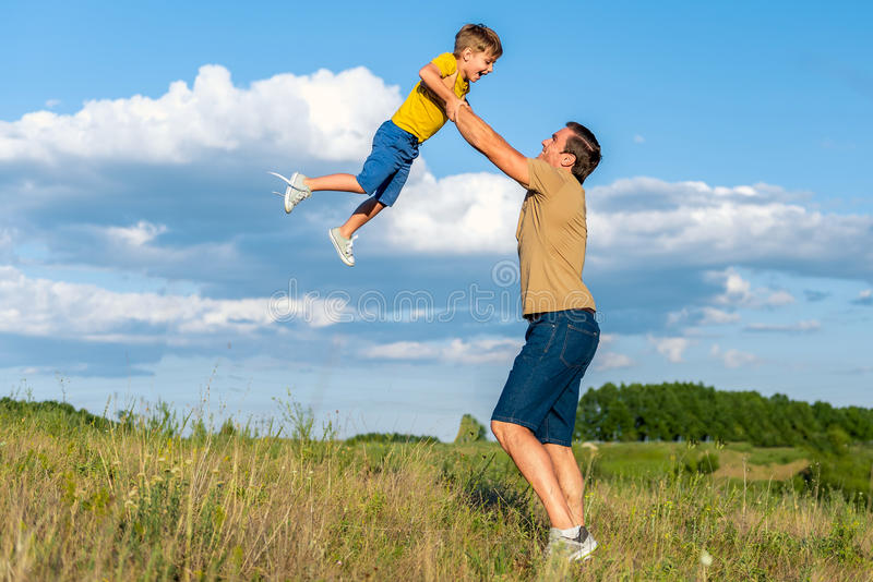 Happy parent playing with child on grassland royalty free stock photo