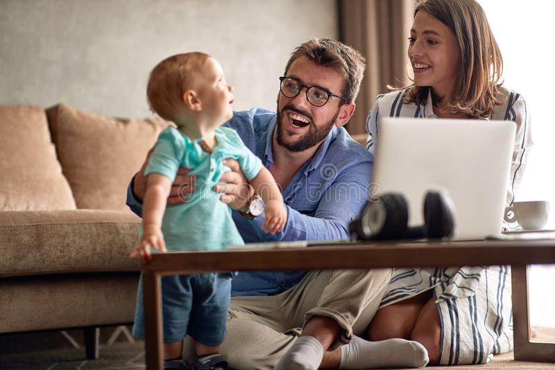 Happy parents with baby working from home using laptop stock photo