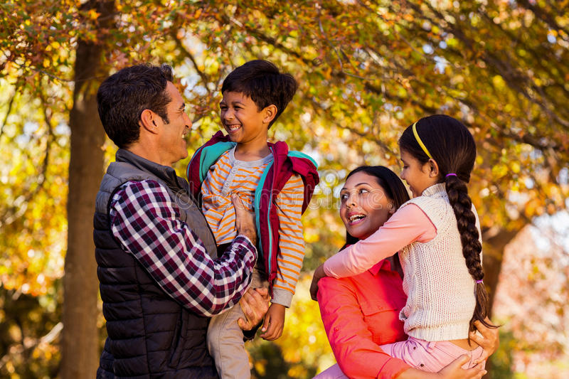 Happy parents carrying children at park royalty free stock image